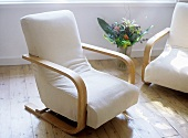 White cotton armchairs with vase of flowers on wooden floor.