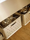 Two stainless steel pull out drawers with stainless steel utensils.