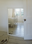 White room with Victorian frame bed reflected in mirror, pair of shoes and wooden floor.sense of space,