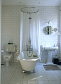 Traditional, white tiled bathroom with a free standing roll top bathtub, chrome.
