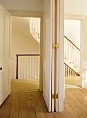 Panelled room divider separating view of hallway with staircase