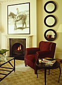A traditional, sitting room with fireplace open fire, velvet upholstered chair, pattern floor, side table,