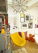 Modern sitting room with white walls, artwork and yellow chair with metal legs.