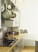 Modern kitchen with white walls, stainless steel cooker and splash back, ceramic hob, grey units, wooden work tops,