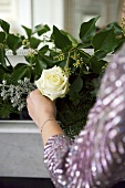 A white rose being held in front of a flower arrangement