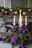 Burning candles in glass candle holders decorated with flowers