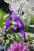 A purple Christmas bauble with a bow hanging from a candle stick
