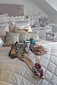 Ladies' shoes on a a white quilt and cushions made of shiny material on a bed