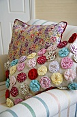 Fabric flowers and a floral pattern on cushions in an upholstered armchair