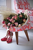 Roses on a 150s style armchair with red shoes on the floor