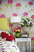Various bunches of flowers on a bedside table against a wall with floral patterned wallpaper