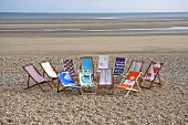 Deckchairs with various patterned fabrics on a beach with a view of the sea