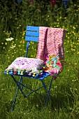 A cushion on a blue metal garden chair