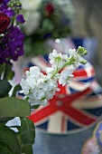 A sprig of white flowers and Union Jack plates in a background