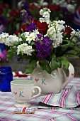 A bunch of flowers in a white ceramic jug and a matching cup