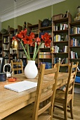 Red amaryllis in a white vase on a wooden dining table with a bookshelf in the background