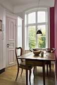 Dining room (country home style) with a rustic table and designer pendant lamp