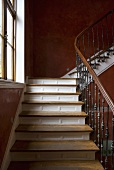 A stairway with a wooden banister and red-brown sponge-painted walls