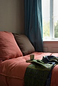 Pink and brown cushions on a bed in front of a window