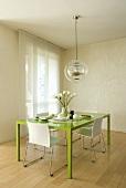 Grüner Esstisch mit Stühlen und Hängelampe im Designerstil