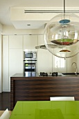 Designer pendant light above a table and open floor plan wooden kitchen unit