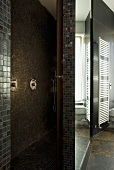A shower area with designer brown and gold mosaic tiles