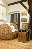 A designer woven armchair with a wooden side table in the corner of a room
