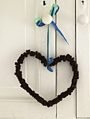 A heart-shaped chain made of nuts and bolts hanging on a door handle