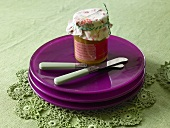 A stack of purple plate on a green tablecloth with a jar of jam and knives