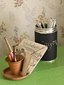 A clay pot and note paper next to a metal pot of coloured pencils