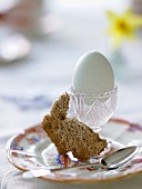 An egg in an egg cup and a piece of rabbit-shaped toast