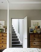 Holzkommode neben offener Tür mit Blick auf Treppe