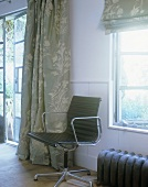 Black office chair in front of a window in a country home