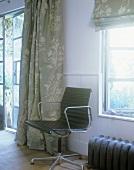 Schwarzer Bürostuhl vor Fenster im Landhaus