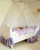 A child's bed with a white, wooden frame and a canopy