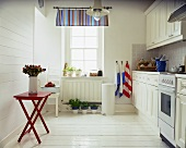 White kitchen in country house style with red folding table