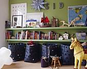 Wandregal und blaue Aufbewahrungsbehälter vor grüner Wand im Kinderzimmer
