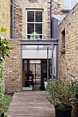 A renovated town house with a brick facade and a conservatory