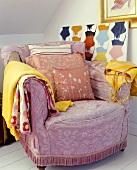 Fliederfarbener Polstersessel mit Kissen und Kleidung