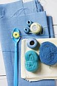 An arrangement comprising blue balls of wool on blue fabric