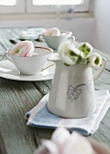 Peonies in a white pitcher and cups with saucers on a wooden plank