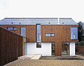 A new house built partially with wood panelling with floor-to-ceiling windows