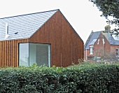 Vertical wood panelling on a newly built house with a corner window and a hedge