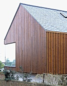 Vertical wood panelling on a newly built house with a corner window