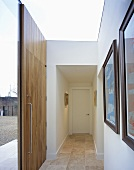 A modern entrance way painted white with a wooden front door