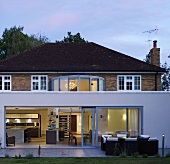 A modern extension in front of a villa with a brick facade