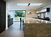 A stone dining table in an open-plan kitchen with terrace windows