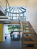 An open stairway with steel steps and a view of a dining table in front of a terrace window