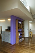 Open-plan living - a bookshelf in front of a purple wall