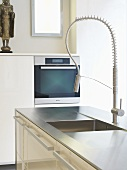 A stainless steel sink with designer taps in a work surface